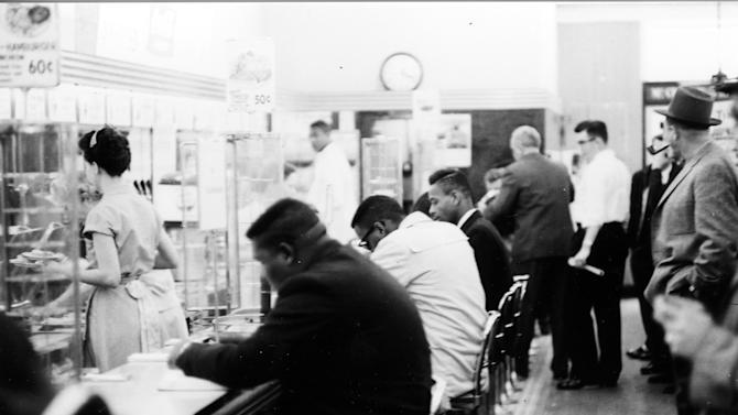 """FILE - In this February 1960 file photo, people take part in a civil rights """"sit-in"""" protest at the lunch counter in McCrory's in Rock Hill, S.C. A prosecutor on Wednesday, Jan. 28, 2015, will argue a motion to vacate the convictions of a group known as the Friendship Nine. Eight Friendship Junior College students and a civil rights organizer were convicted of trespassing and breach of peace for staging a similar protest at the same lunch counter in 1961. The men opted for a month's hard labor rather than allow bail to be posted for them by civil rights groups. (AP Photo/The Herald, File)"""