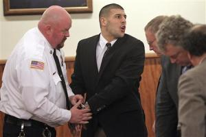 Former New England Patriots player Aaron Hernandez mouths words with family members after he appeared in court at the Fall River Justice Center in Fall River
