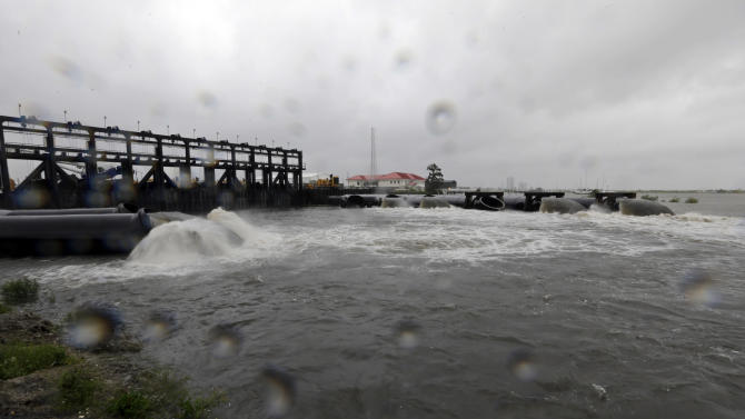 FILE - In this Aug. 29, 2012 file photo, water flows out of the new 17th Street Canal pumping station as Hurricane Isaac hits in New Orleans. By the time the next hurricane season starts in June 2013, New Orleans will take control of much of a revamped protection system of gates, walls and armored levees the Army Corps of Engineers has spent about $12 billion building. The corps has about $1 billion worth of work left. Engineers consider it a Rolls Royce of flood protection, comparable to systems in seaside European cities such as Venice and Rotterdam. (AP Photo/David J. Phillip, File)
