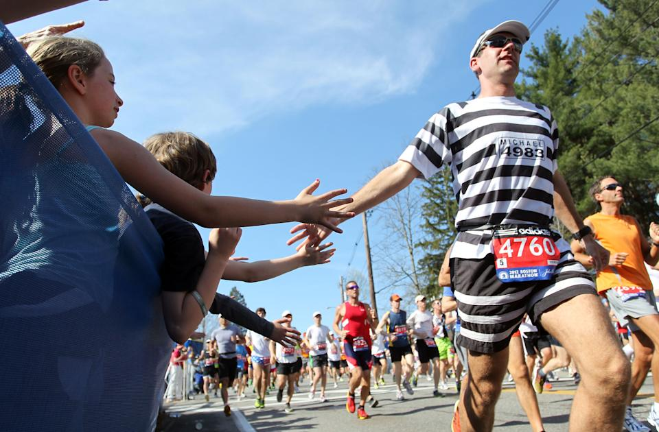Michael Leibold, from Germany, reaches out to spectators at the start of the 116th running of the Boston Marathon, in Hopkinton, Mass., Monday, April 16, 2012. (AP Photo/Stew Milne)