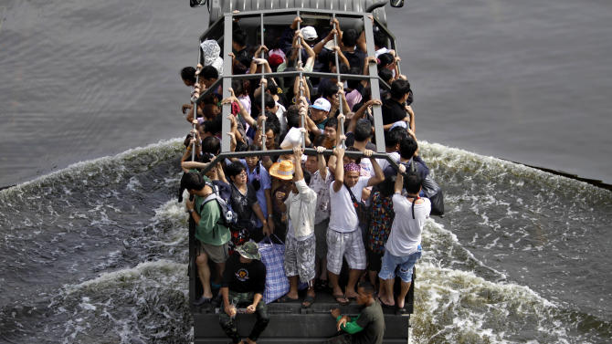 Thai residents are transported on a military truck through a flooded street in Bangkok, Thailand, Saturday, Nov. 5, 2011. Floodwaters lapped Bangkok's largest outdoor market Saturday as officials warned that there were no major barriers between the water and the heart of the Thai capital, less than 6 miles (10 kilometers) away. (AP Photo/Altaf Qadri)