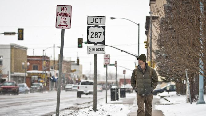 Laramie resident Leeds Butler walks down the sidewalk along Grand Avenue during an early afternoon snowfall in Laramie, Wyo., Tuesday, April 9, 2013. (AP Photo/Laramie Boomerang, Jeremy Martin)