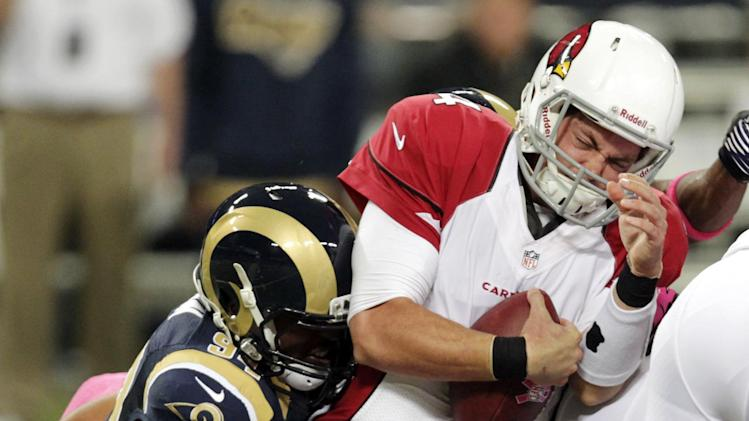 Arizona Cardinals quarterback Kevin Kolb, right, carries the ball as St. Louis Rams defensive end Robert Quinn tackles during the first quarter of an NFL football game, Thursday, Oct. 4, 2012, in St. Louis. (AP Photo/Tom Gannam)