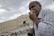 <p>A striking teacher addresses marchers as they pass the Greek parliament on Wednesday.</p>