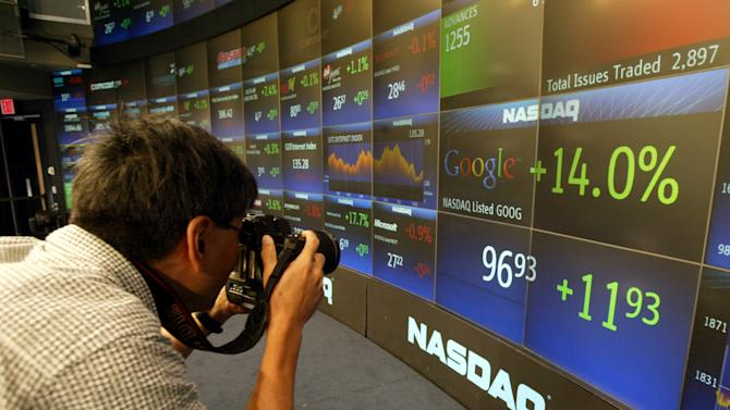 FILE- In this Aug. 19, 2004 file photo, a photographer makes pictures of the board at the Nasdaq Marketsite in New York's Times Square shortly after shares of Google started trading. Google's IPO 10 years ago launched the company on a trajectory that continues to reshape its business and much of the world in its orbit. (AP Photo/Kathy Willens, File)