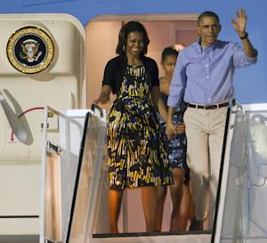 President Barack Obama, right, and first lady Michelle Obama, left, along with their daughter Sasha, center back, disembark Air Force One after arriving at Joint Base Pearl Harbor-Hickam for their family Christmas vacation, Friday, Dec. 20, 2013, in Honolulu. The first family will be spending their vacation in Hawaii and return to Washington on Jan. 5, 2014. (AP Photo/Eugene Tanner)