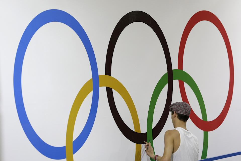 Worker Aaron Scotney applies the Olympic rings to a wall in the ExCel Center in preparation for the 2012 Summer Olympics, Thursday, July 26, 2012, in London. (AP Photo/Hassan Ammar)