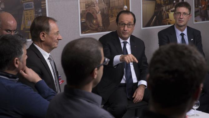 French President Francois Hollande speaks with ArcelorMittal workers as he visits their union meeting room during a visit at the ArcelorMittal Steel Factory in Florange