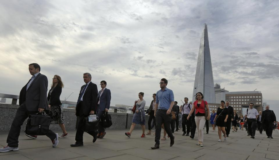 Commuters walk across London Bridge to the City of London
