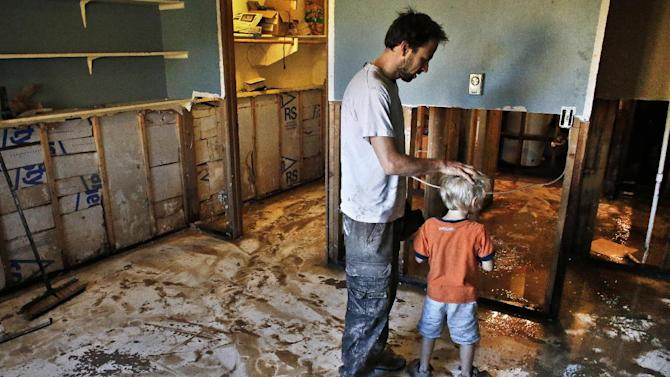 Local resident Chad Obrien comforts his four year old son Elijah, as he works to remove waterlogged and contaminated floors and walls from his flooded basement, which was wrecked in recent flooding, in Longmont, Colo., Wednesday Sept. 18, 2013. As water recedes and flows east onto the Colorado plains, rescuers are shifting their focus from emergency airlifts to trying to find the hundreds of people still unaccounted for after last week's devastating flooding. (AP Photo/Brennan Linsley)