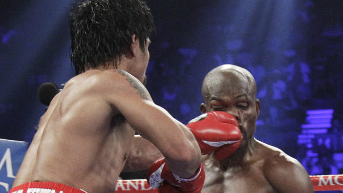 Manny Pacquiao, from the Philippines, left, lands a punch to the face of Timothy Bradley, from Palm Springs, Calif., in the fourth round of their WBO welterweight title fight Saturday, June 9, 2012, in Las Vegas. (AP Photo/Julie Jacobson)