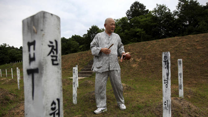 """In this Thursday, June 28, 2012 photo, Mukgai, a South Korean who goes by his Buddhist name and plans to become a monk, offers a prayer for buried North Korean and Chinese soldiers who died in the Korean War at the """"enemy cemetery,""""  south of the Demilitarized Zone in Paju, South Korea. Hundreds of identical wooden grave markers poke out of the grass on the hill surrounded by rice paddies and trees, North Korea's dark mountains visible in the distance. Some are rotting; some have been knocked to the dirt; most have no names.  (AP Photo/Hye Soo Nah)"""