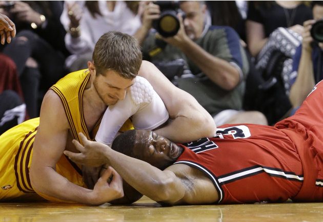 Cleveland Cavaliers center Tyler Zeller, left, and Miami Heat guard Dwyane Wade battle for a loose ball during the first half of an NBA basketball game, Sunday, Feb. 24, 2013, in Miami. (AP Photo/Wilf