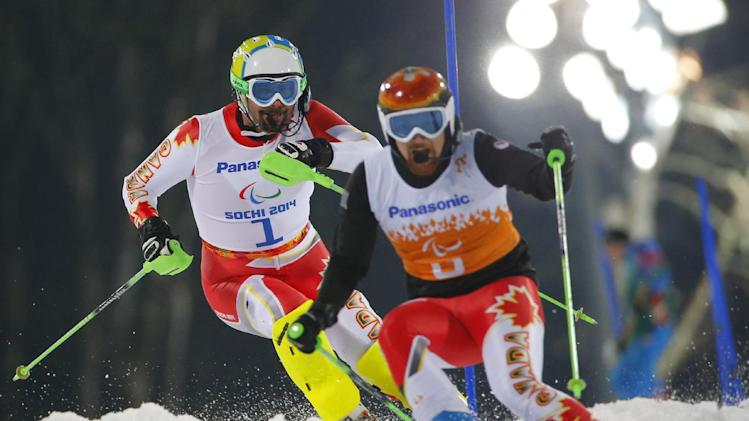 Chris Williamson of Canada, left, and his guide Nick Brush compete during the men's alpine skiing, slalom, visually impaired event at the 2014 Winter Paralympic, Thursday, March 13, 2014, in Krasnaya Polyana, Russia