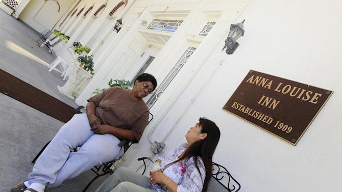 Residents Sherene Julian, right, and Robin Howard talk on the porch outside the Anna Louise Inn, Monday, Sept. 24, 2012, in Cincinnati. Western & Southern Financial Group wants the 103 year old home for women to leave the picturesque downtown neighborhood that they share in favor of a boutique hotel. (AP Photo/Al Behrman)