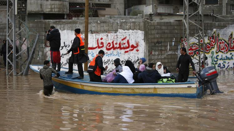 Members of the Palestinian civil defense ride a boat as they evacuate people on a stormy day in Gaza City