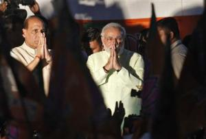 Narendra Modi and Rajnath Singh greet party supporters after Modi was crowned BJP's prime ministerial candidate in New Delhi