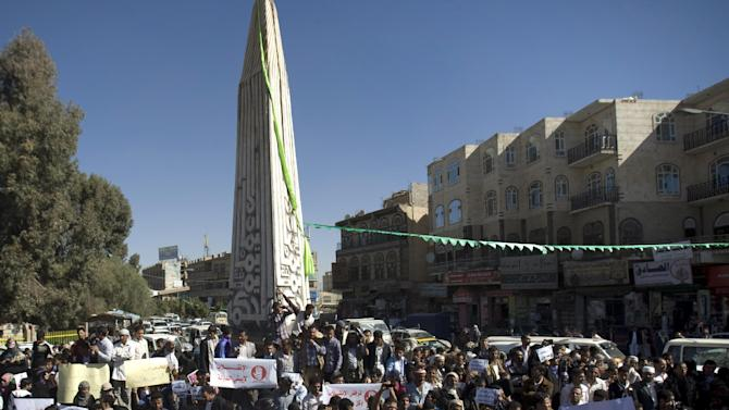 "Protesters hold posters against Houthi Shiite rebels who hold the capital, Sanna, amid a power vacuum as they hold a demonstration in Sanaa on Saturday, Jan. 24, 2015. Some 20,000 marched Saturday across the capital, where demonstrators converged on the house of President Abed Rabbo Mansour Hadi, who resigned Thursday along with his Cabinet. Arabic writing on the banner at right reads, ""Militias do not build a country."" (AP Photo/Hani Mohammed)"