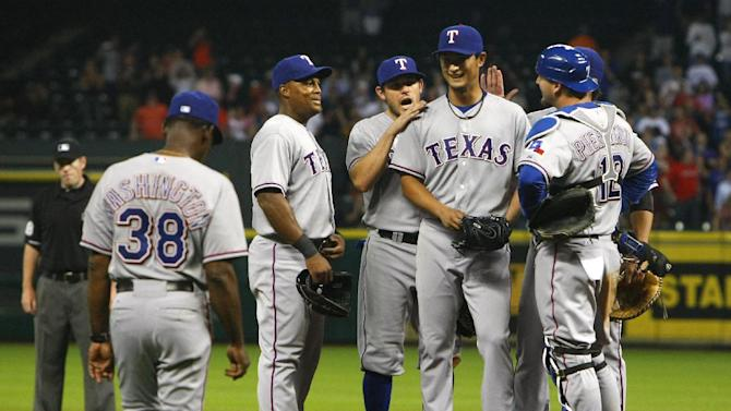 Texas Rangers starting pitcher Yu Darvish, center, smiles after pitching a no-hitter into the ninth inning of a baseball game against the Houston Astros Tuesday, April 2, 2013, in Houston. (AP Photo/Houston Chronicle, Cody Duty)