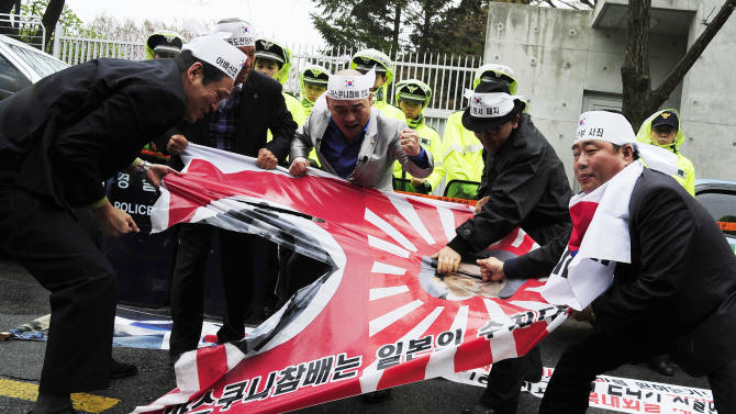 South Korean protesters tear a Japanese wartime flag during a rally to protest against Japanese lawmakers' visit to Yasukuni Shrine, which honors Japan's war dead, including World War II leaders convicted of war crimes, in front of the residence of Japanese ambassador in Seoul, South Korea, Tuesday, April 23, 2013. Dozens of Japanese lawmakers paid homage at a national war shrine Tuesday morning, risking more anger from neighbors South Korea and China over visits they see as failures to acknowledge Japan's militaristic past.(AP Photo)