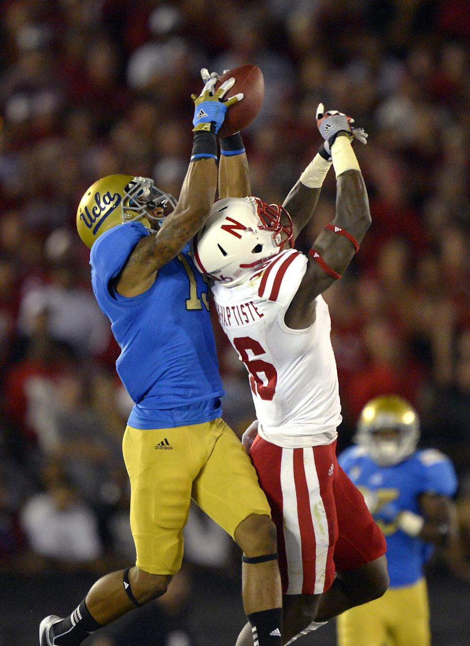 UCLA wide receiver Devin Lucien, left, catches a pass as Nebraska cornerback Stanley Jean-Baptiste defends during the second half of their NCAA football game, Saturday, Sept. 8, 2012, in Pasadena, Calif.   UCLA won 36-30. (AP Photo/Mark J. Terrill)