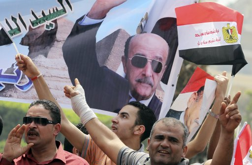 Supporters of presidential candidate and Egypt's former vice president Omar Suleiman, cheer while carrying banners bearing images of him, as Suleiman presented recommendation do*****ents to the (HPEC) headquarters in Cairo
