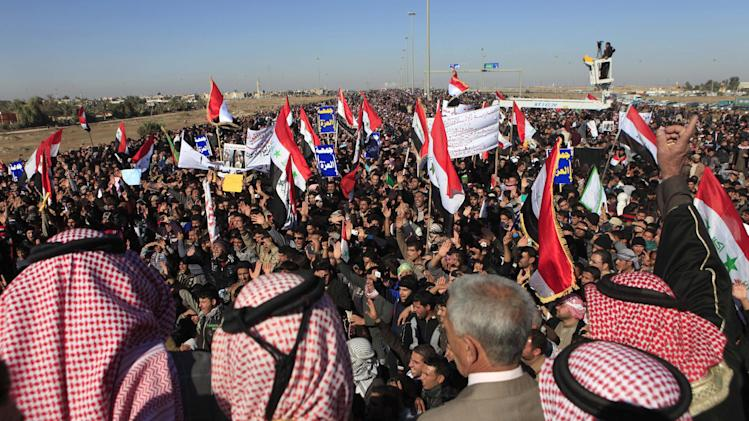 Protesters chant slogans against Iraq's Shiite-led government as they wave national flags during a demonstration in Fallujah, 40 miles (65 kilometers) west of Baghdad, Iraq, Friday, Dec. 28, 2012. Thousands of Iraqi Sunnis massed along a major western highway and in other parts of the country Friday for what appear to be the largest protests yet in a week of demonstrations, intensifying pressure on the Shiite-led government. (AP Photo/ Karim Kadim)