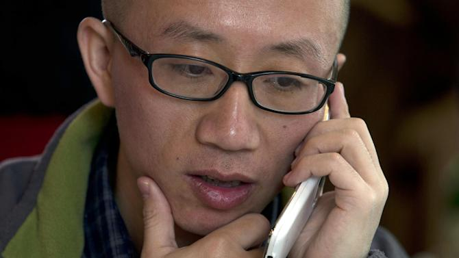 """In this photo taken Wednesday, April 10, 2013, Chinese dissident Hu Jia talks on his phone during a meeting at a restaurant in Beijing, China. In prosecuting the country's political and social activists, an image-conscious Beijing is shifting its tactics. Rather than filing charges of inciting state subversion that amount to political prosecution and drawing international condemnations, Beijing is increasingly using public disorder charges to lock up those it considers as nuisances or threats to its rule. Hu describes this system as """"craftier and crueler."""" (AP Photo/Ng Han Guan)"""