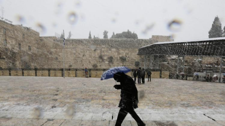 A man holding an umbrella walks as snow falls at the Western Wall in Jerusalem's Old City