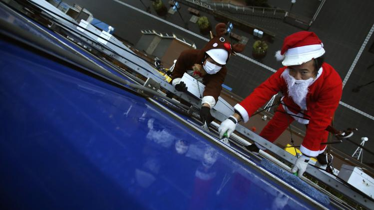 Window cleaners dressed as Santa Claus and a reindeer pose for photographers at an event to celebrate Christmas at a shopping mall in Tokyo