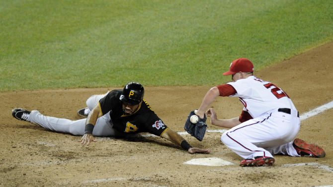 Pittsburgh Pirates' Pedro Alvarez, left, slides home to score on a wild pitch against Washington Nationals relief pitcher Drew Storen (22) during the eighth inning of a baseball game, Monday, July 22, 2013, in Washington. The Pirates won 6-5. (AP Photo/Nick Wass)