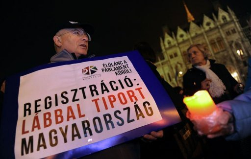"<p>A participant holds a banner reading, ""Registration: Trampled Hungary"" in front of the parliament building in Budapest. Over a thousand people formed a human chain around the Hungarian parliament building on Monday in protest of a government shake-up of the country's electoral system.</p>"