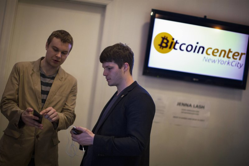 Austin Alexander, deputy director of Bitcoin Center New York City (R) talks about his digital wallet with an attendee during the Satoshi Square at the...