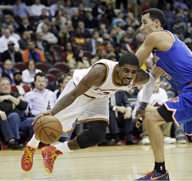 Cleveland Cavaliers' Kyrie Irving, left, falls as he drives past New York Knicks' Pablo Prigioni, from Argentina, in the fourth quarter of an NBA basketball game Tuesday, Dec. 10, 2013, in Cle