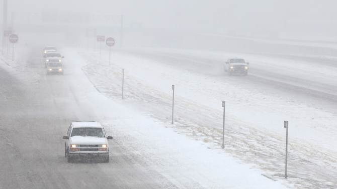 Vehicles move along in blizzard conditions in Lubbock, Texas, Monday, Feb. 25, 2013.  State troopers are unable to respond to calls for assistance and National Guard units are mobilizing as a winter storm blankets the central Plains with a foot of snow in some places. Roads are closed Monday throughout West Texas and the Panhandle. (AP Photo/Lubbock Avalanche-Journal, Zach Long)