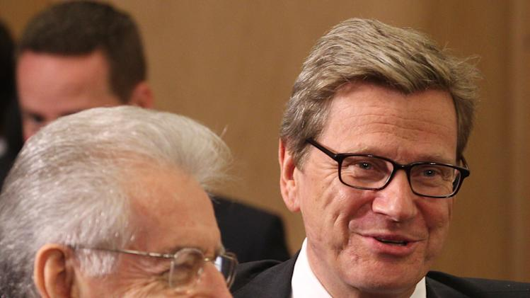 Italy's Foreign Minister Mario Monti, left, talks with German Foreign Minister Guido Westerwelle prior to the NATO-Russia Council during a NATO foreign ministers meeting at NATO headquarters in Brussels, Tuesday, April 23, 2013. (AP Photo/Yves Logghe)