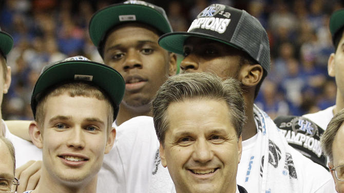 Kentucky head coach John Calipari and Kentucky players pose for a photo with the trophy after defeating Baylor, 82-70 in an NCAA tournament South Regional finals college basketball game Sunday, March 25, 2012, in Atlanta. (AP Photo/David J. Phillip)