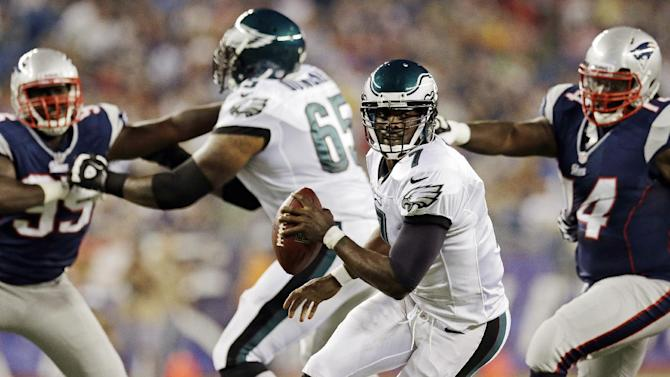 Philadelphia Eagles quarterback Michael Vick, center, tries to elude New England Patriots defensive tackle Kyle Love, right, as Patriots defensive end Chandler Jones, left, is held back by Eagles tackle King Dunlap during the first quarter of an NFL preseason football game in Foxborough, Mass., Monday, Aug. 20, 2012. (AP Photo/Elise Amendola)