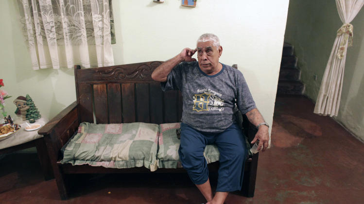 In this photo taken April 30, 2013, Jose Pastano, 71, speaks during an interview at his house in Caracas, Venezuela. In a country evenly split between the ruling party and opposition, countless families have been torn apart by political divisions. The retired bus mechanic chided his children for backing Venezuela's opposition, calling them ungrateful for all that the late President Hugo Chavez had done for the country during his 14 years in power. (AP Photo/Ariana Cubillos)