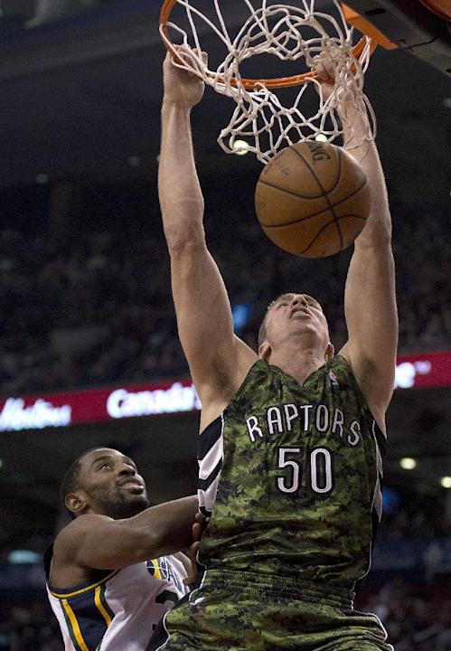 Toronto Raptors forward Tyler Hansbrough (50) dunks the ball against Utah Jazz forward Mike Harris during the first half of an NBA basketball game in Toronto on Saturday, Nov. 9, 2013