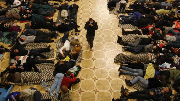 A man walks past protesters resting in Kiev's City Hall, now an organisational hub for protesters who have occupied the building