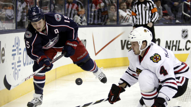 Columbus Blue Jackets' Derek Dorsett, left, passes the puck in front of Chicago Blackhawks' Niklas Hjalmarsson of Sweden in the second period of an NHL hockey game in Columbus, Ohio, Saturday, Jan. 26, 2013. (AP Photo/Paul Vernon)