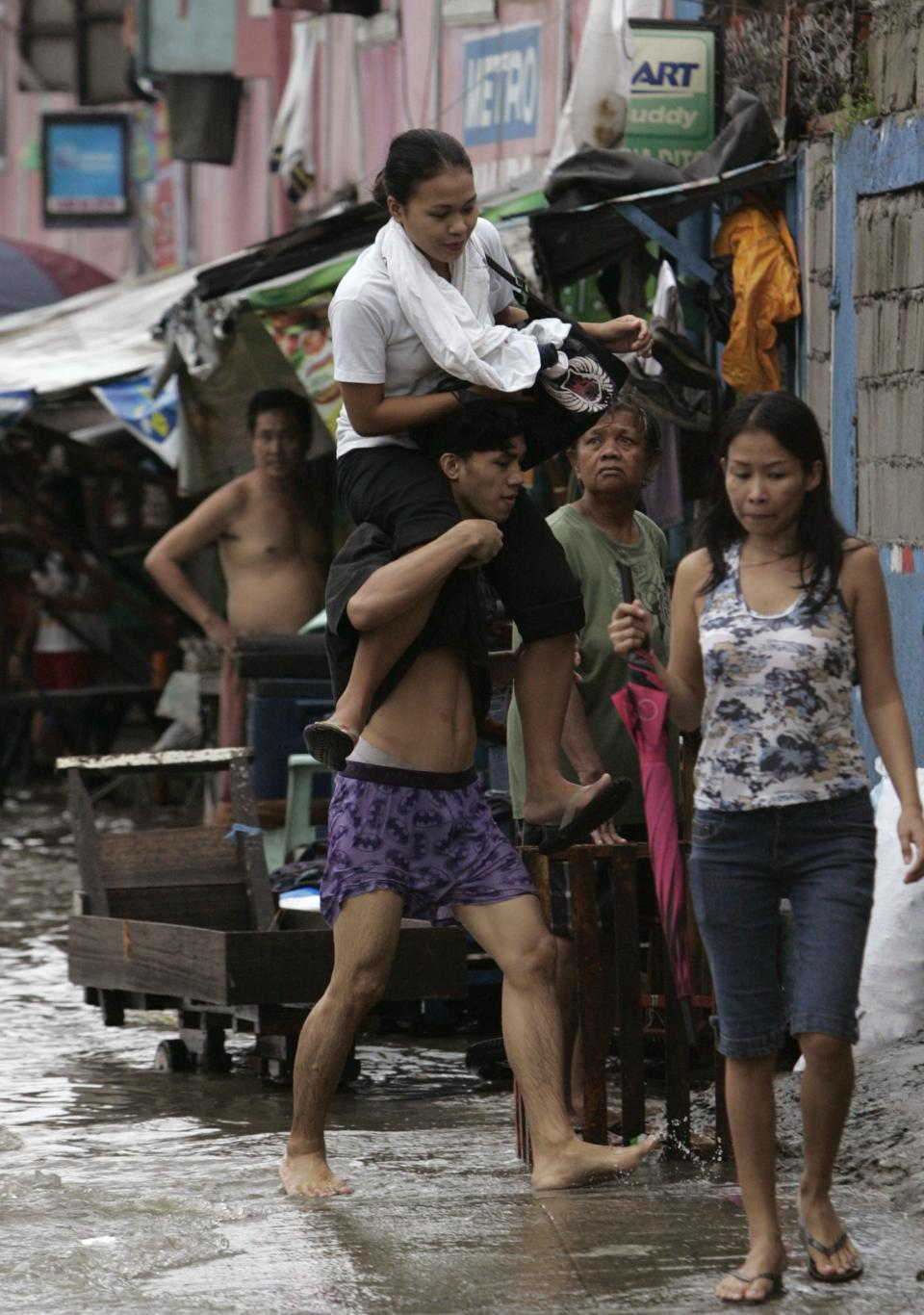 A woman rides on the man's shoulder to keep her feet dry from the flood water Tuesday, Aug. 2, 2011 in suburban Quezon City, north of Manila, Philippines. Waist-deep floods have swamped the streets in the Philippine capital after a night of monsoon rains closed down schools and government offices.  (AP Photo/Pat Roque)