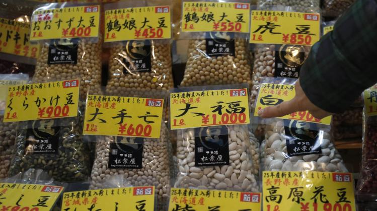 A shopper points at a pack of beans in a food store at a shopping district in Tokyo