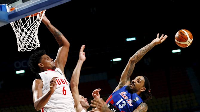 Cuba's Javier Justiz and teammate Orestes Torres jump for the ball with Puerto Rico's Ronaldo Balkman during their 2015 FIBA Americas Championship basketball game