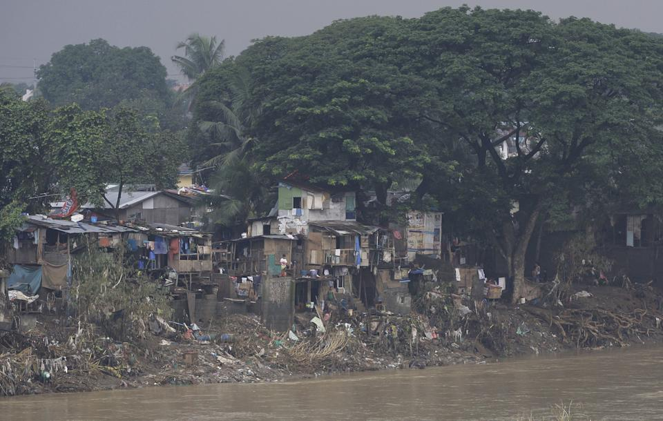 Debris lay outside houses built along the riverbanks in suburban San Mateo, Rizal province, east of Manila, Philippines on Tuesday, Aug. 14, 2012. The government is still grappling with the aftermath of a massive flooding when tropical storm Kai-Tak blew in affecting the country's northeast. (AP Photo/Aaron Favila)