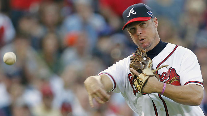 Atlanta Braves third baseman Chipper Jones (10) fields a ball hit by St. Louis Cardinals' Yadier Molina during the  inning of the National League wild card playoff baseball game on Friday, Oct. 5, 2012, in Atlanta. Molina was out at first. (AP Photo/John Bazemore)