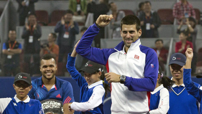 "Serbia's Novak Djokovic, front, performs South Korean rapper PSY's "" Gangnam Style"" dance with volunteers while Jo-Wilfried Tsonga of France, second from left, looks on after a prize presentation for their men's singles final match of the China Open tennis tournament in Beijing Sunday, Oct. 7, 2012. Djokovic won the China Open tennis tournament, defeated Tsonga 7-6, 6-2. (AP Photo/Andy Wong)"