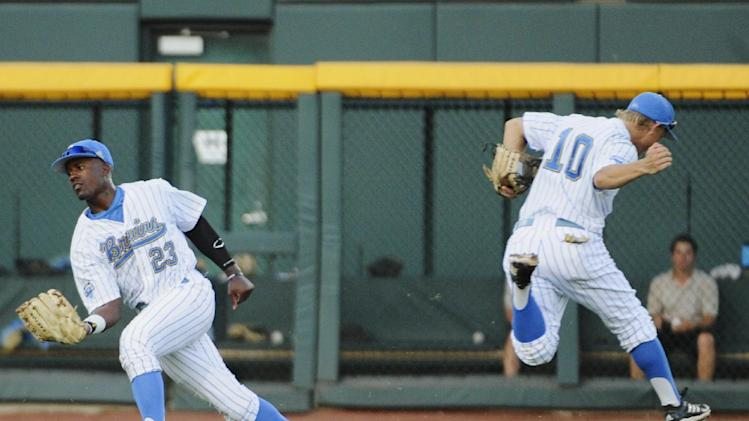 UCLA left fielder Brenton Allen (23) catches a fly ball hit by North Carolina's Parks Jordan as shortstop Pat Valaika (10) runs in the opposite direction in the third inning of an NCAA College World Series baseball game in Omaha, Neb., Friday, June 21, 2013. (AP Photo/Francis Gardler)