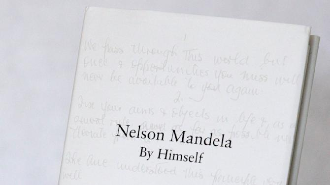"""A copy of former South African president Nelson Mandela's newly released book, titled Nelson Mandela By Himself, is held up for a photograph in Johannesburg, South Africa, Monday, June 27, 2011. A new Nelson Mandela book, slim, bound in black and set in eye-straining type, looks a bit like a bible or a prayer book. That's fitting, because the editors of """"Nelson Mandela By Himself"""" brought something close to religious zeal to the task of choosing and checking more than 2,000 quotations to ensure the world gets the anti-apartheid icon's words right. (AP Photo/Themba Hadebe)"""